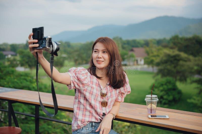 采取与她的照相机的小姐旅客selfie在自然美好的风景 免版税库存图片