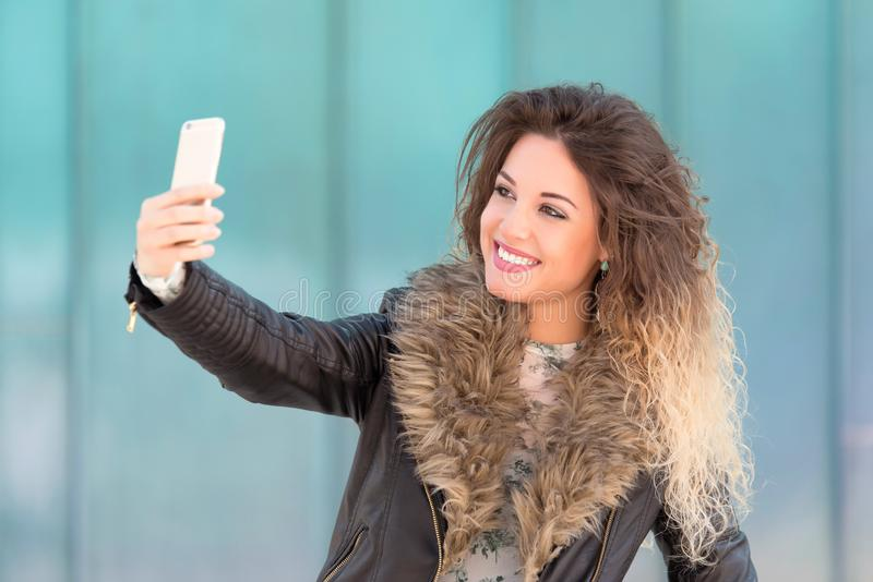 采取与她的电话的少女selfie 库存图片