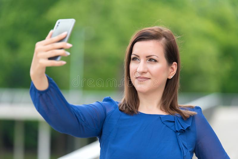 采取与她的电话的年轻女人一selfie 库存图片