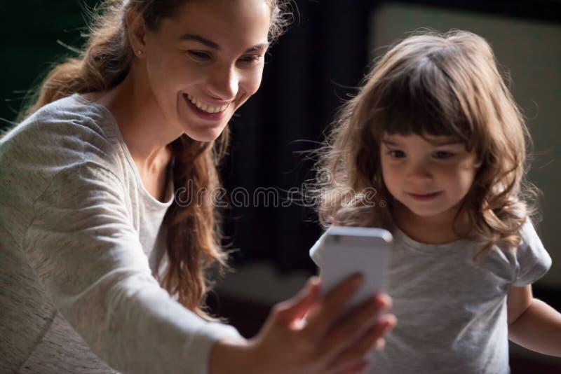 采取与孩子女儿的微笑的母亲selfie智能手机的 免版税库存图片
