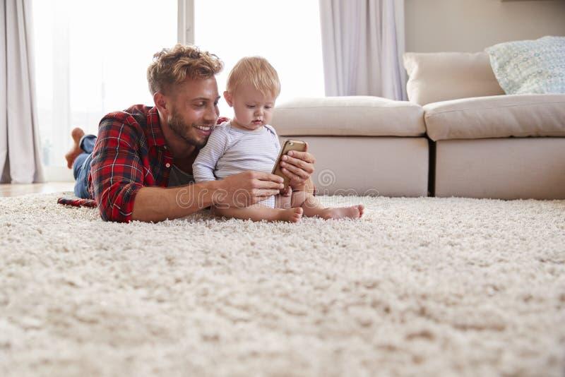 采取与小孩儿子的年轻父亲selfie在客厅 免版税库存图片