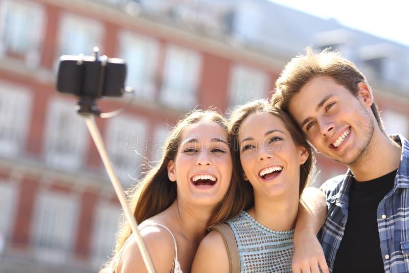 采取与巧妙的电话的小组旅游朋友selfie 库存图片