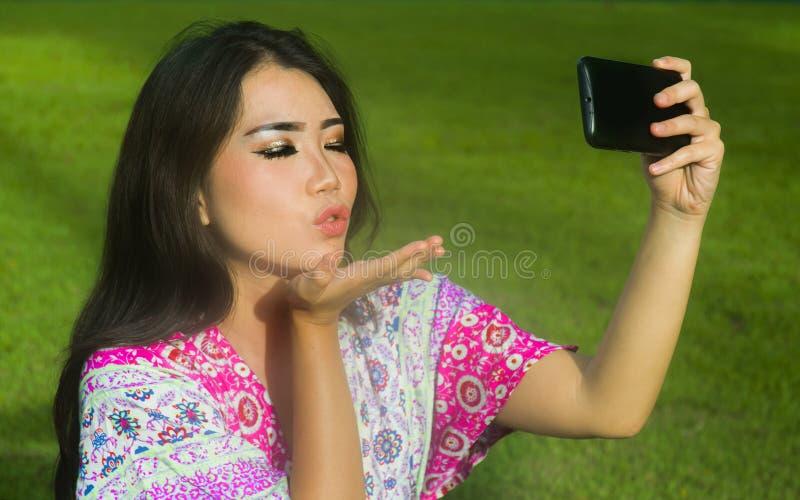 采取与手机照相机的年轻愉快和美丽的亚裔中国妇女selfie pic投掷摆在户外在绿色的亲吻 免版税图库摄影