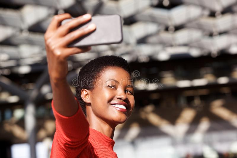 采取与手机照相机的微笑的年轻非洲妇女selfie 免版税库存照片