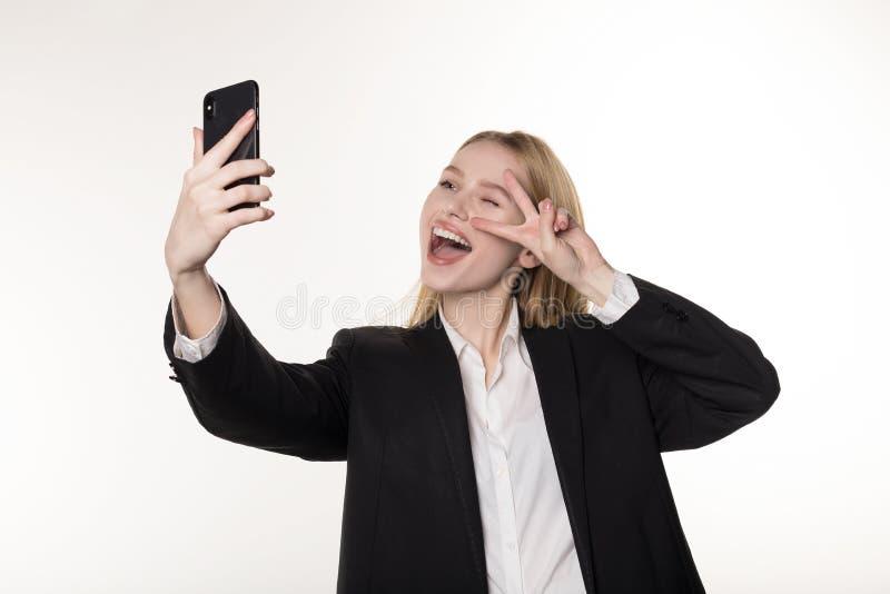 采取与手机的一名微笑的白肤金发的女实业家的画象的腰部selfie 免版税库存图片