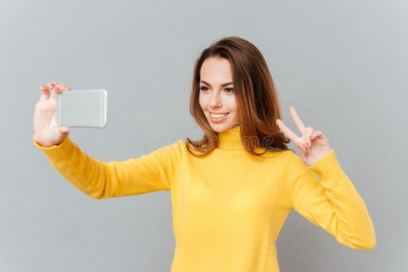采取与手机的可爱的嬉戏的少妇selfie 免版税库存照片