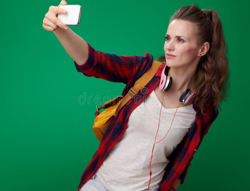 采取与手机的年轻学生妇女selfie 免版税库存照片