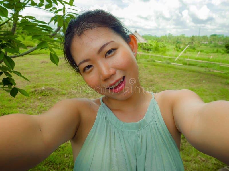 采取与手机的年轻愉快和可爱的亚裔中国妇女selfie自画象在热带海岛摆在快乐 免版税图库摄影