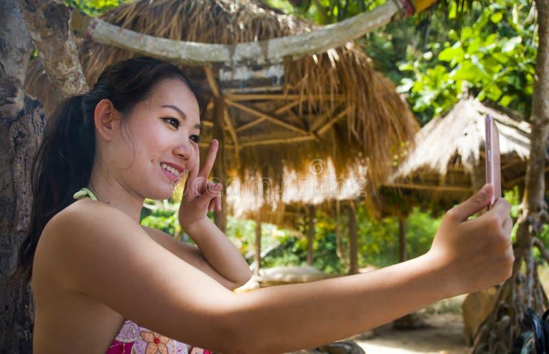采取与手机的年轻美丽和愉快的亚裔韩国妇女自画象selfie在热带天堂海滩胜地 免版税库存图片