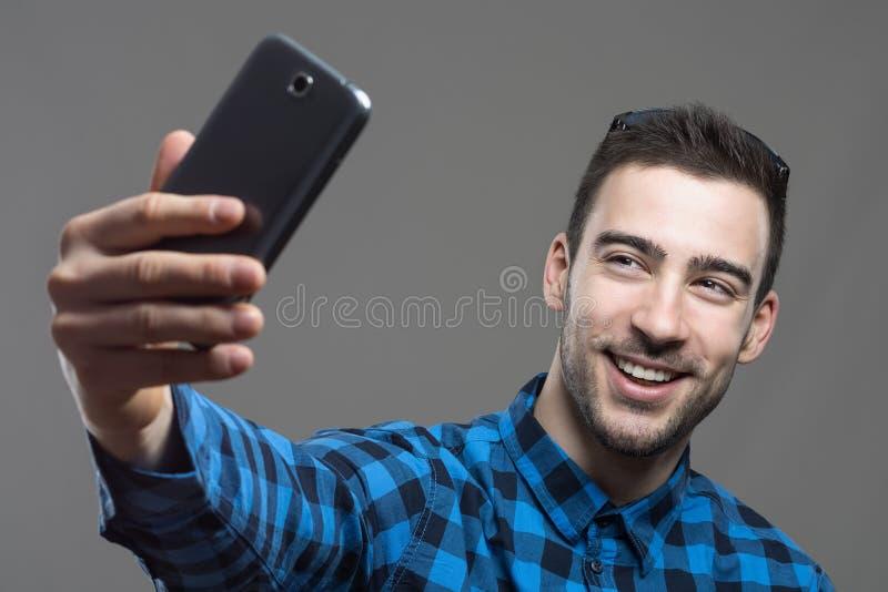 采取与手机的激动的年轻微笑的人自画象 库存图片
