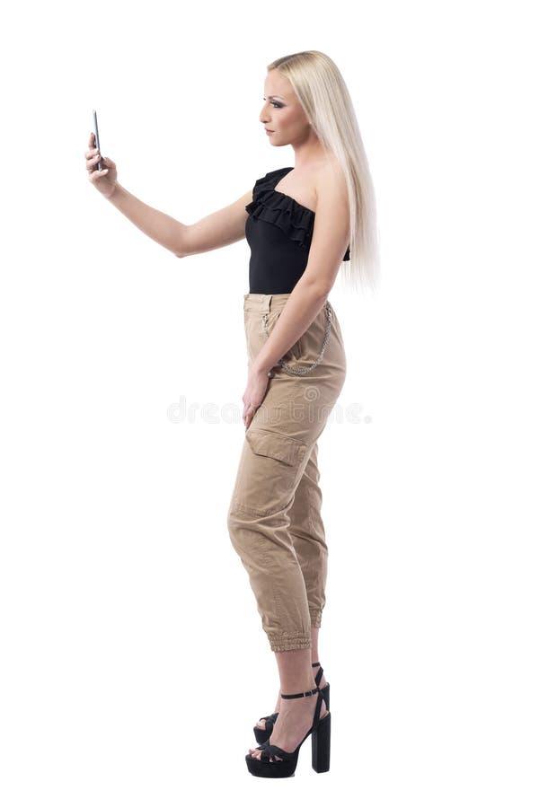 采取与手机的确信的现代白肤金发的时兴的时髦的妇女侧视图selfie 图库摄影