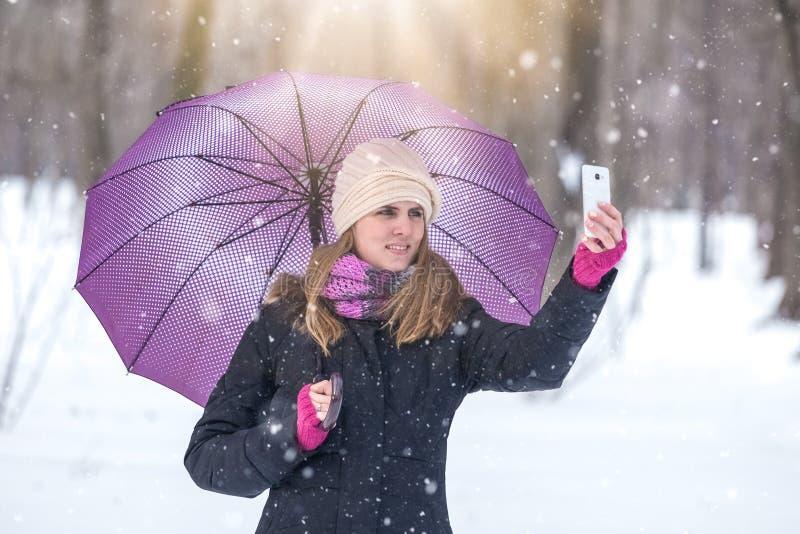 采取与手机的美丽的少妇自画象在多雪的天 免版税库存照片