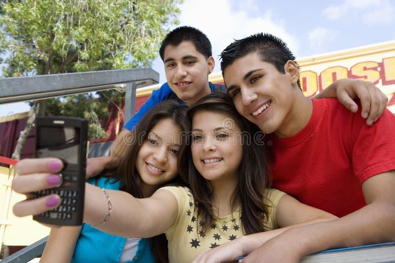 采取与手机的高中朋友自画象 库存图片