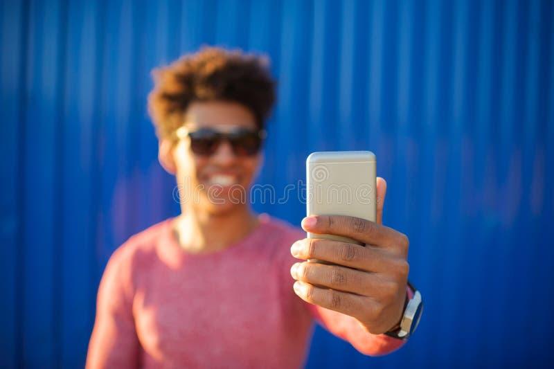 采取与手机的年轻人自画象 免版税库存照片