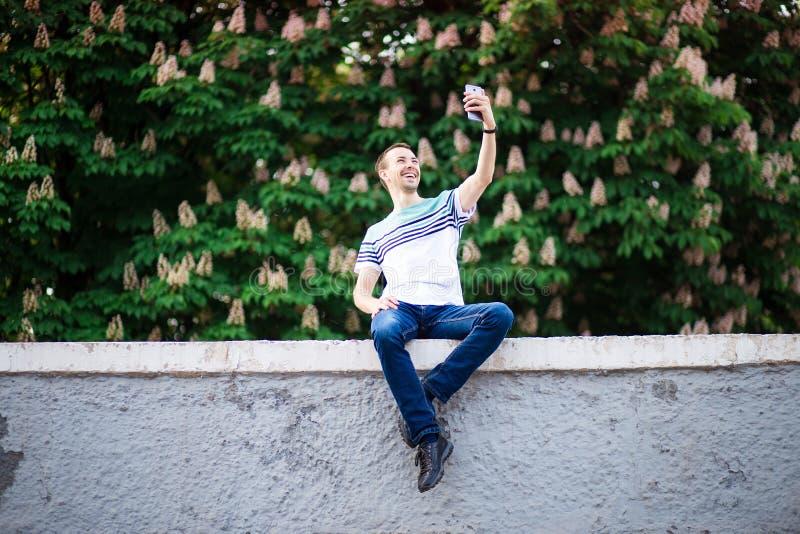 采取与智能手机户外的时兴的年轻巴黎人一selfie在公园在晴朗的夏日 免版税库存图片