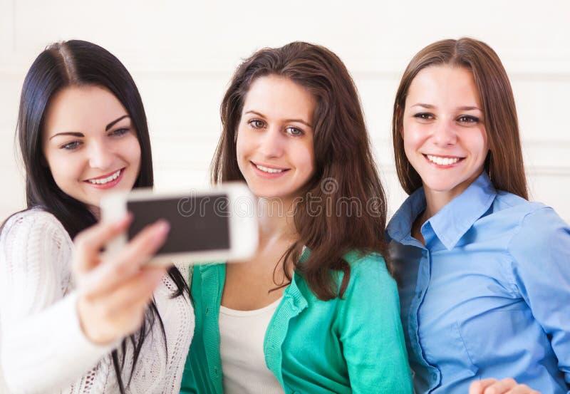 采取与智能手机照相机的三个微笑的十几岁的女孩selfie 免版税库存照片