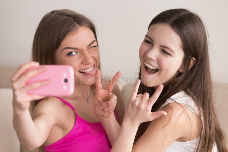 采取与智能手机的两个年轻愉快的女朋友selfie 免版税图库摄影