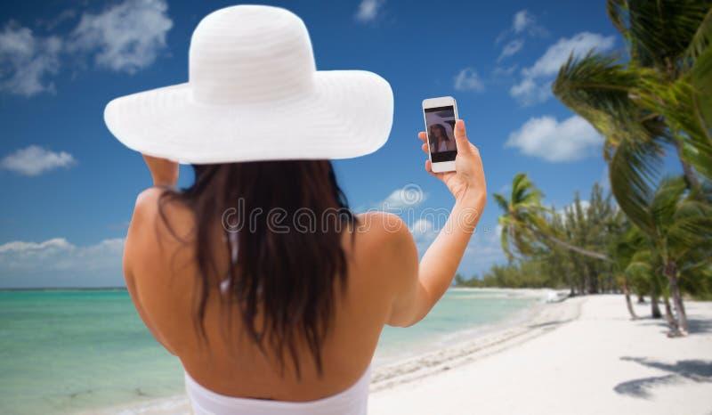 采取与智能手机的妇女selfie在海滩 免版税库存图片