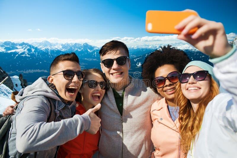 采取与智能手机的微笑的朋友selfie 免版税图库摄影