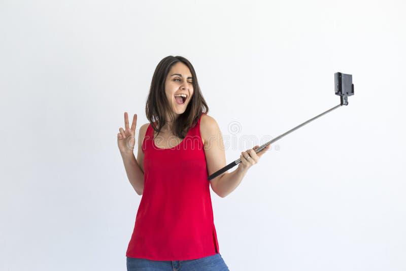 采取与智能手机的愉快的美女一selfie在白色背景 生活方式 佩带的便衣和微笑 库存照片