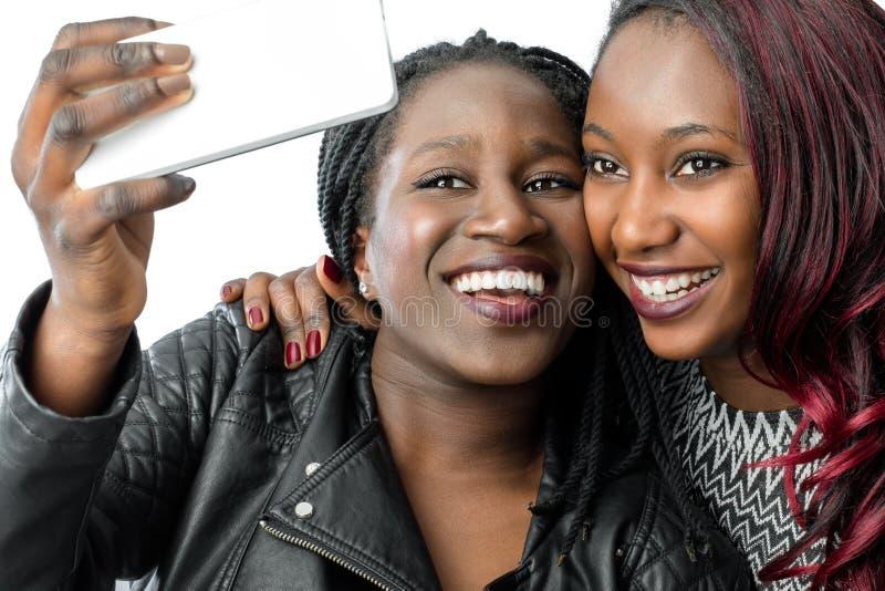 采取与智能手机的非洲青少年的女孩自画象 免版税图库摄影
