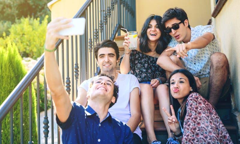 采取与智能手机的年轻愉快的人民一selfie 免版税库存照片