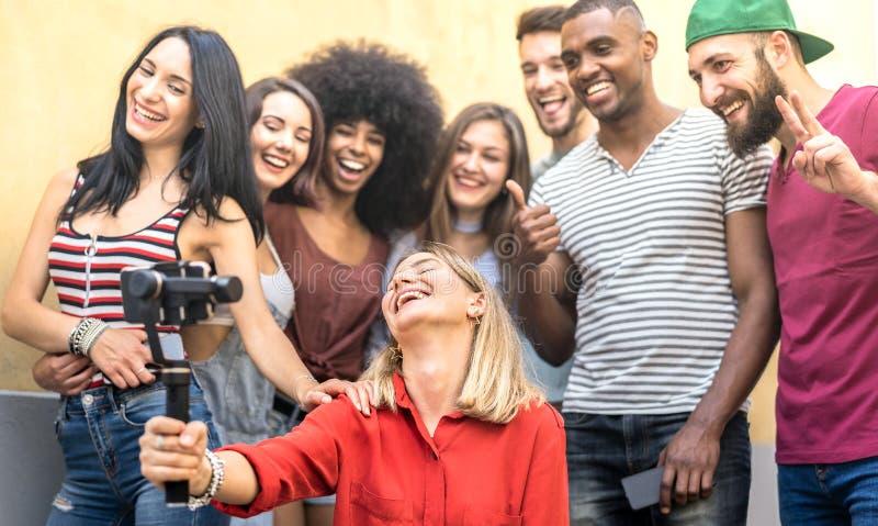 采取与流动智能手机和安定器常平架-与millenial人民的友谊概念的多种族年轻朋友selfie 库存照片