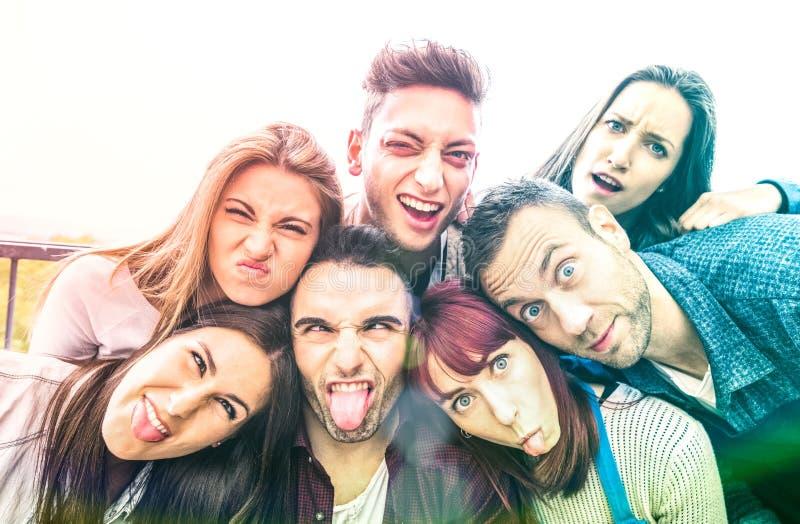 采取与滑稽的面孔的多文化millenial朋友selfie -与千福年的年轻趋向的愉快的青年友谊概念 免版税库存照片