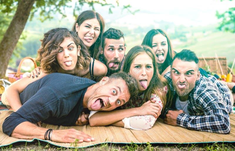 采取与滑稽的面孔的Millenial朋友selfie在pic nic烤肉-与千福年的年轻人的愉快的青年友谊概念 库存照片
