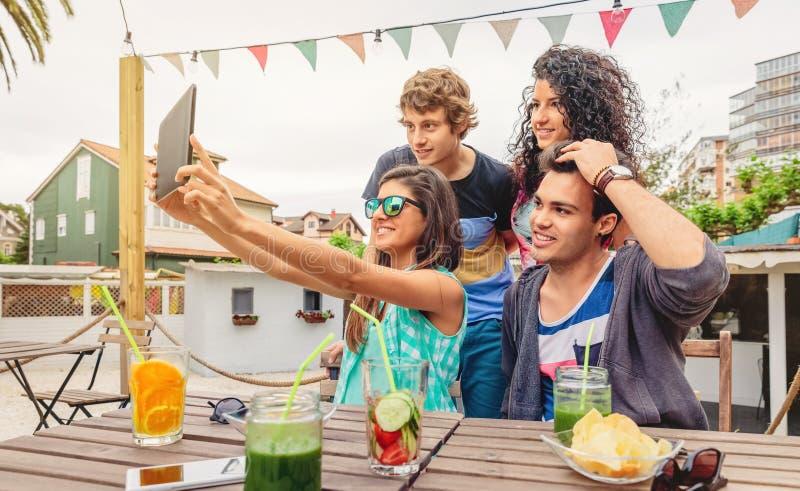 采取与片剂的小组青年人一selfie 免版税库存图片