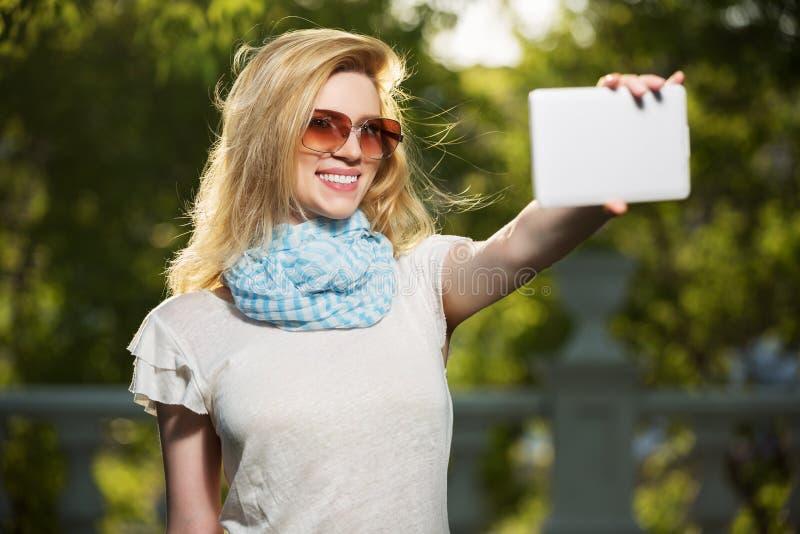 采取与片剂计算机的年轻时尚妇女selfie 免版税图库摄影