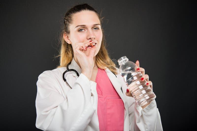 采取与瓶的女性医生药片水 免版税库存图片