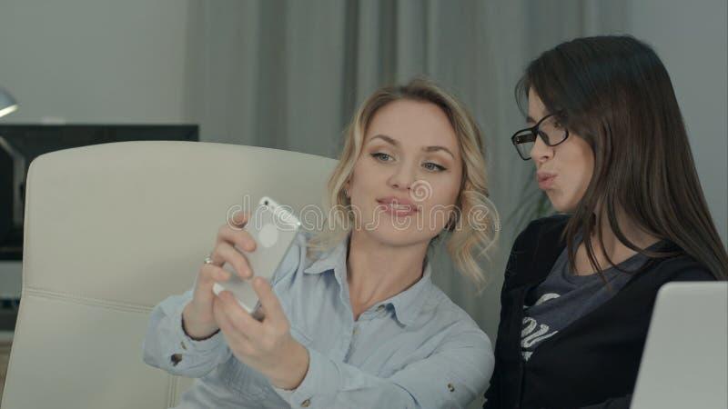 采取与电话的两个女性同事selfies坐在书桌 库存图片
