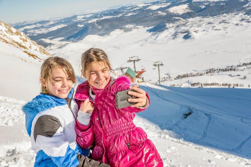 采取与电话的两个小女孩selfie在雪 免版税库存图片
