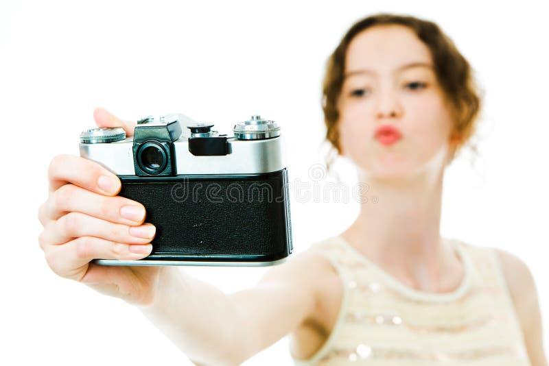 采取与葡萄酒模式照相机的年轻亭亭玉立的女孩selfie -亲吻 免版税库存照片