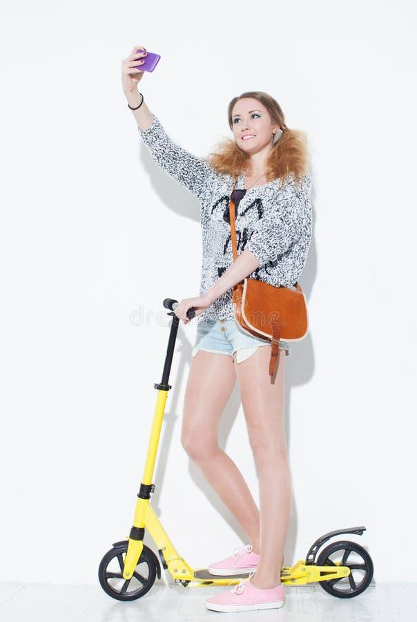 采取与葡萄酒袋子的美丽的时兴的白肤金发的女孩一疯狂的乐趣selfie在他的肩膀 站立在一辆黄色滑行车 clos 免版税库存照片