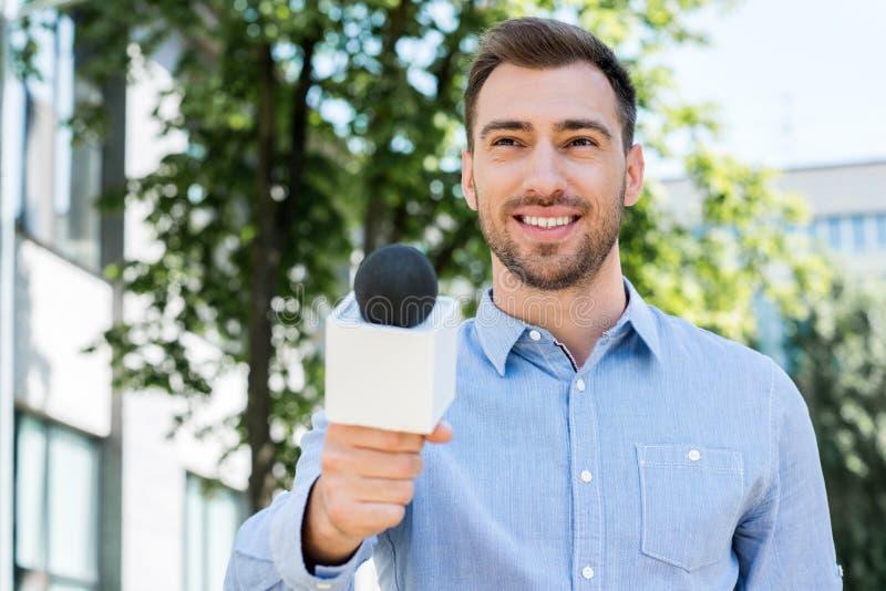 采取与话筒的微笑的男性新闻工作者采访 免版税库存图片