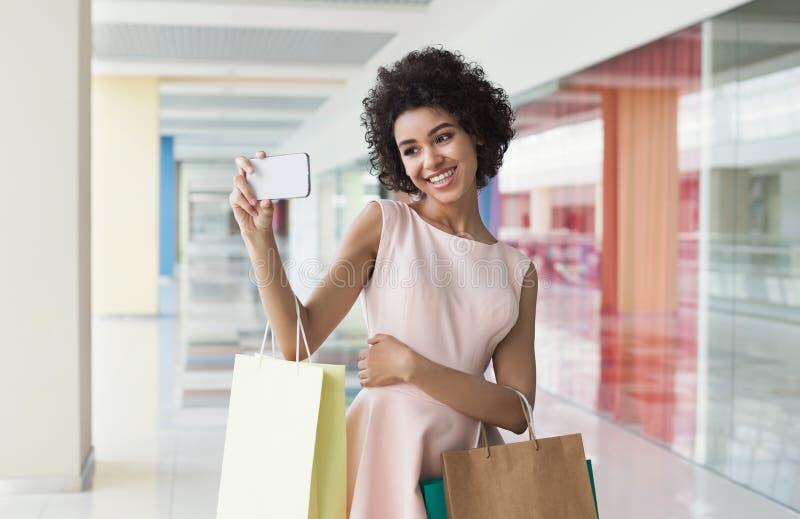 采取与购物袋的逗人喜爱的非裔美国人的妇女selfie 免版税库存图片