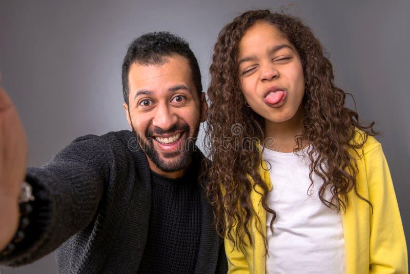 采取与他的女儿的黑人父亲selfies 免版税库存图片