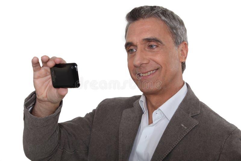 采取与他的cameraphone的人 库存照片