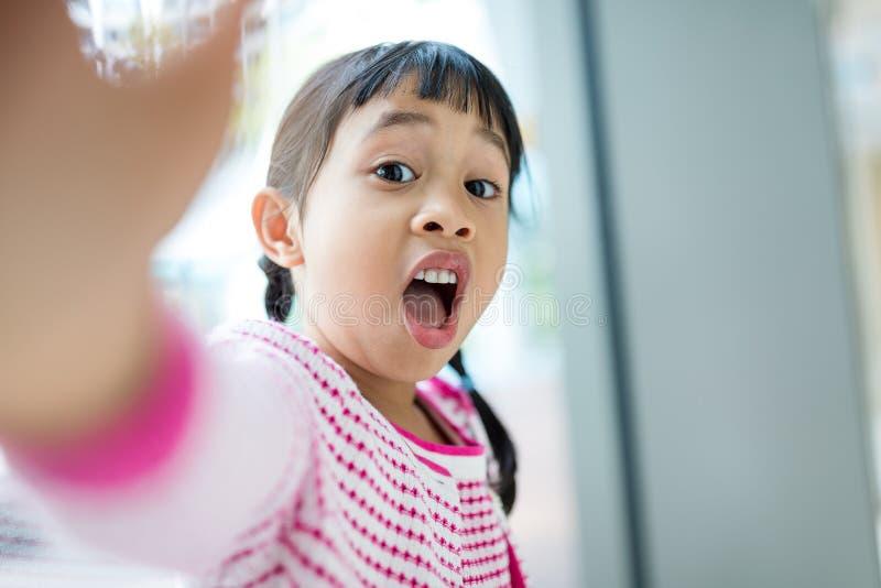 采取与滑稽的表情的小女孩selfie 免版税库存照片