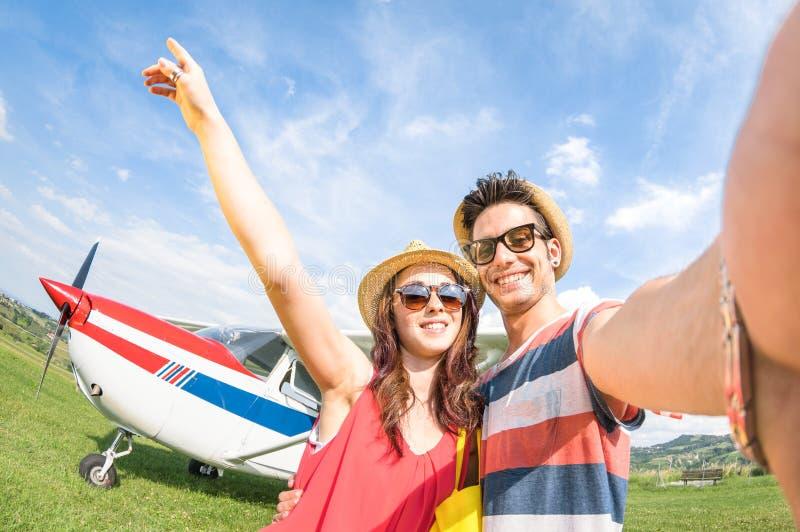 采取与轻量级飞机的年轻夫妇selfie 图库摄影