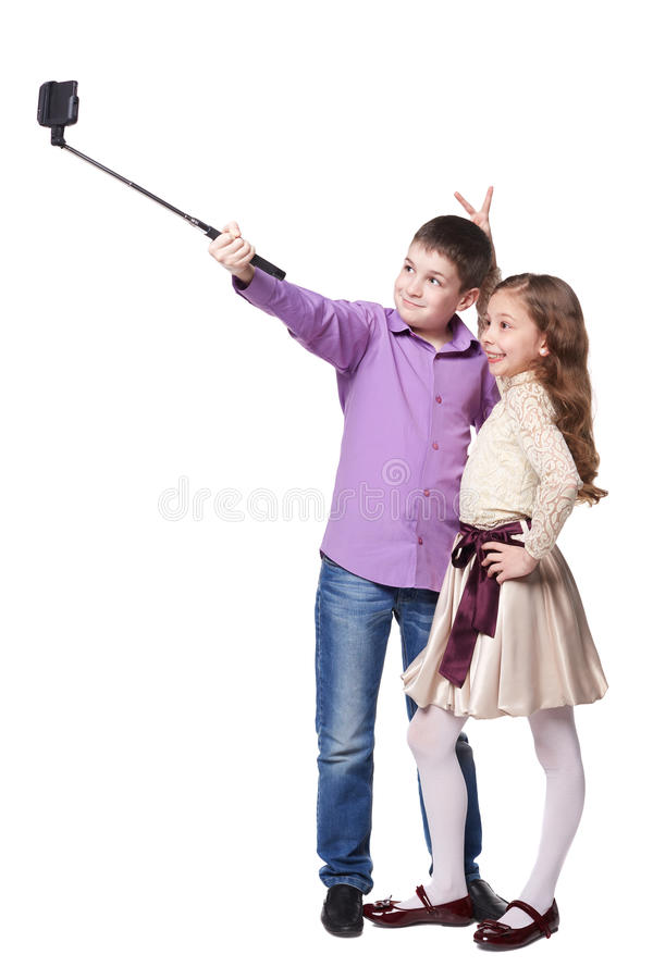 采取与selfiestick的男孩和女孩selfies  免版税库存照片