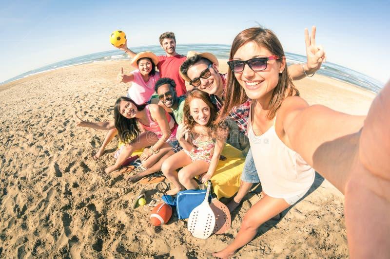 采取乐趣selfie的小组多种族愉快的朋友在海滩 免版税库存图片
