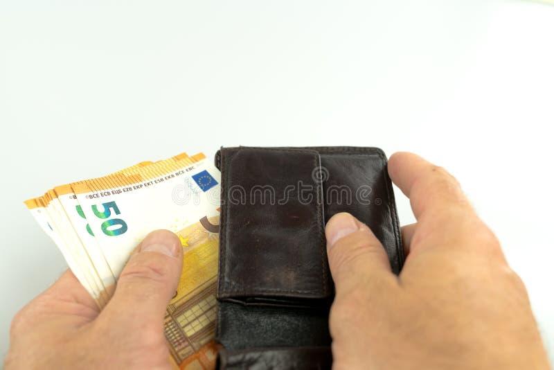 采取五十张欧元钞票的人在一个棕色皮革钱包外面 库存照片