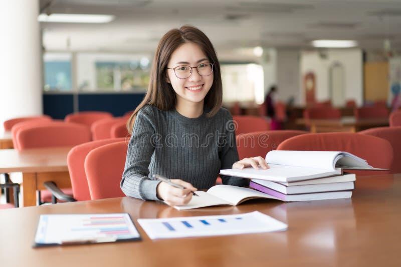 采取从书的女学生笔记在图书馆,坐在桌上的年轻亚裔妇女做任务在大学图书馆里 免版税库存照片