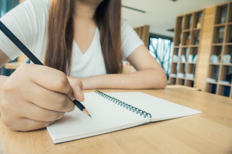 采取从书的女学生笔记在图书馆 坐在桌上的年轻亚裔妇女做任务在大学图书馆里 免版税库存照片
