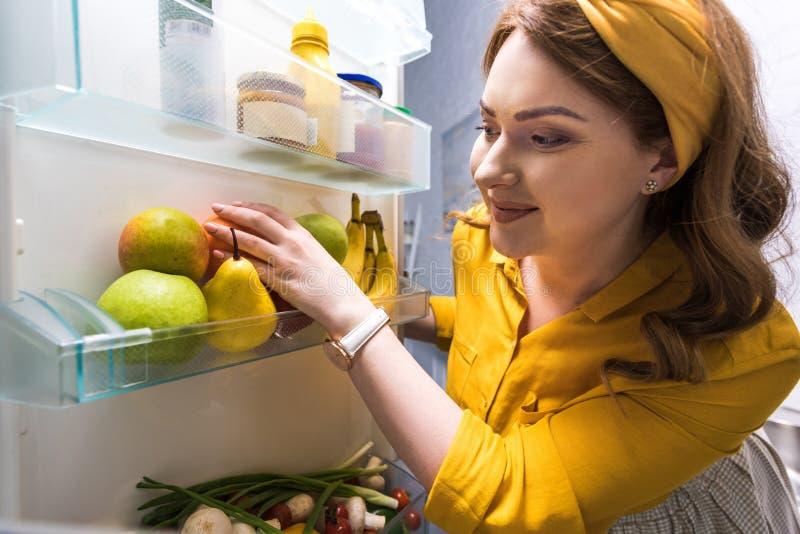 采取从冰箱的美女果子 库存照片
