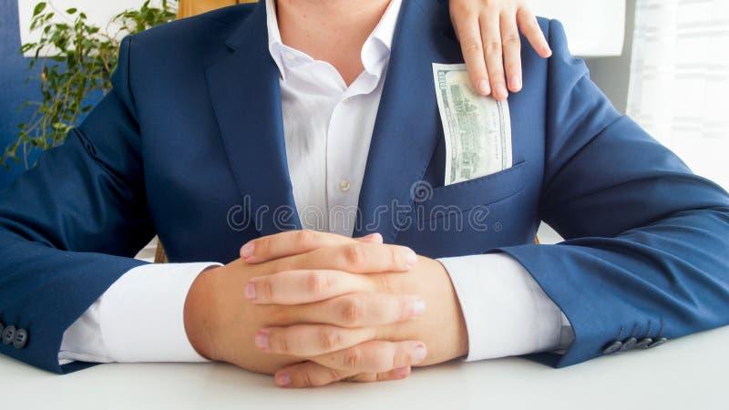 采取从她的丈夫` s夹克口袋的妻子的特写镜头图象金钱 免版税库存照片