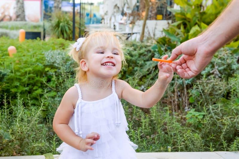 采取从她的父亲的礼服的逗人喜爱的矮小的情感blondy小孩女孩红萝卜快餐在步行期间在城市公园 健康的食物 免版税库存照片